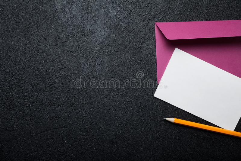 Pencil, envelope and sheet of paper on a black vintage background. Copy space stock photo