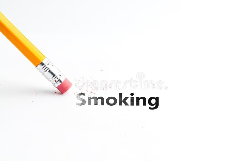 Pencil with eraser. Closeup of pencil eraser and black smoking text. Pencil with eraser. Yellow pencil stock image
