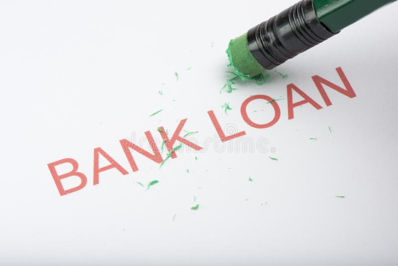 Pencil Erasing the Word `Bank Loan` on Paper royalty free stock photos