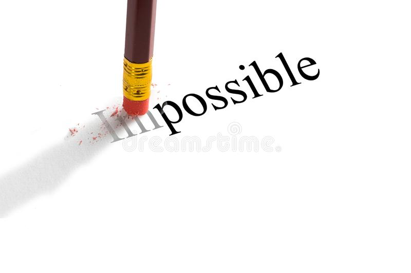 Pencil eraser trying to remove the word `impossible` on paper. Concept. royalty free stock photos