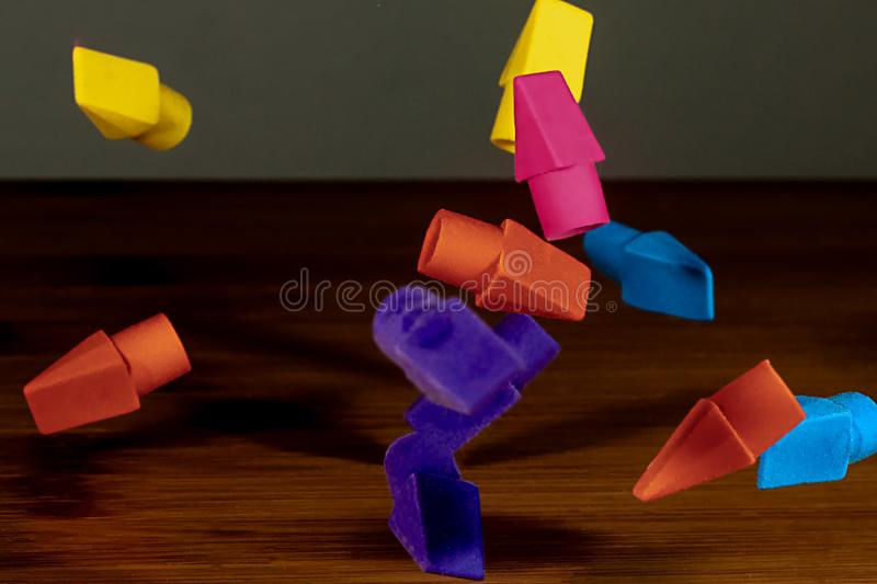 Pencil erasers caught in mid fall cascading onto a wooden deskt. Op royalty free stock images