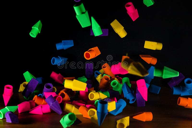 Pencil erasers caught in mid fall cascading onto a wooden deskt. Op stock image