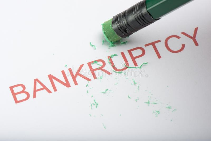 Pencil Erasing the Word `Bankruptcy` on Paper stock photography