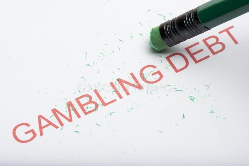 Pencil Erasing the Word `Gambling Debt` on Paper stock image