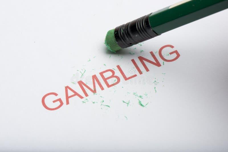 Pencil Erasing the Word `Gambling` on Paper stock image