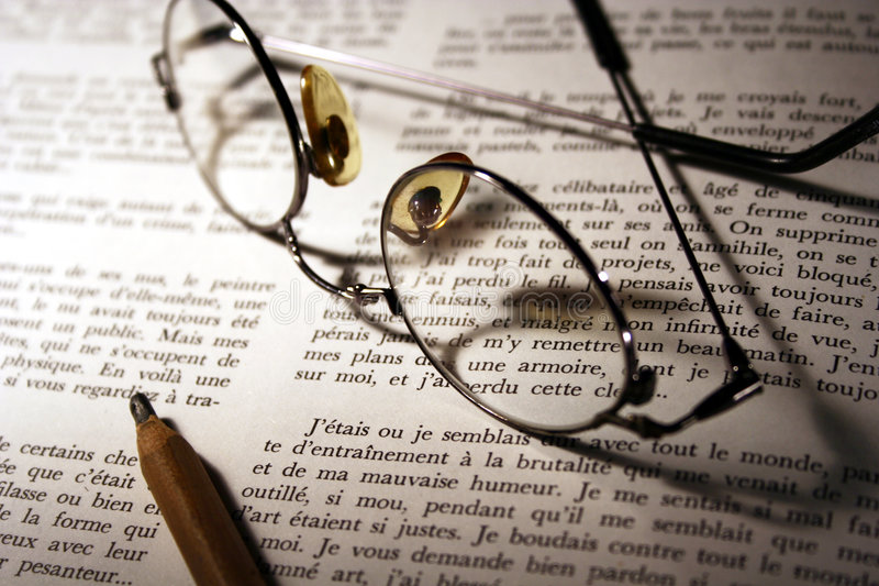 Pencil & Glasses Over Opened Book stock photography