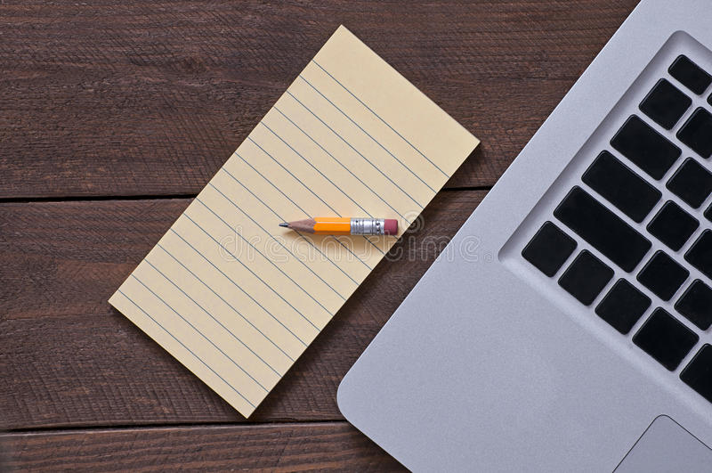 Pencil on the note pad and the computer royalty free stock photography