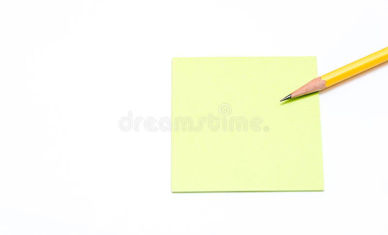 Pencil and note paper on white background. Sharpened pencil on top of a note paper white background royalty free stock photo