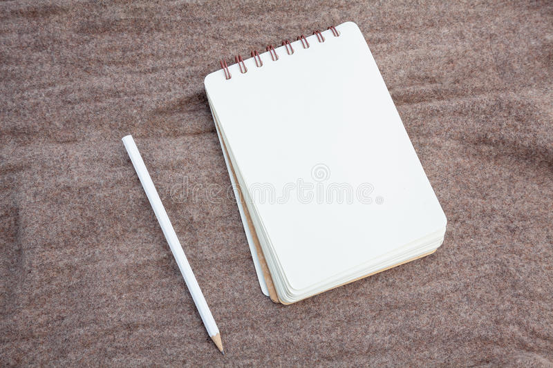 Pencil and notebook. Opened notebook and white pencil stock photo