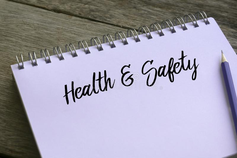 Pencil and notebook written with Health And Safety on wooden background stock images