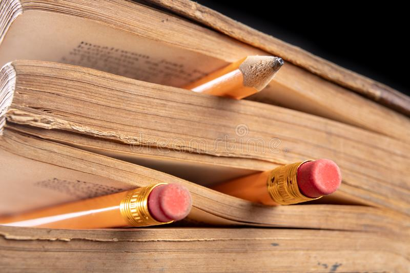 Pencil and old book. Writing accessories and books on an old table stock images