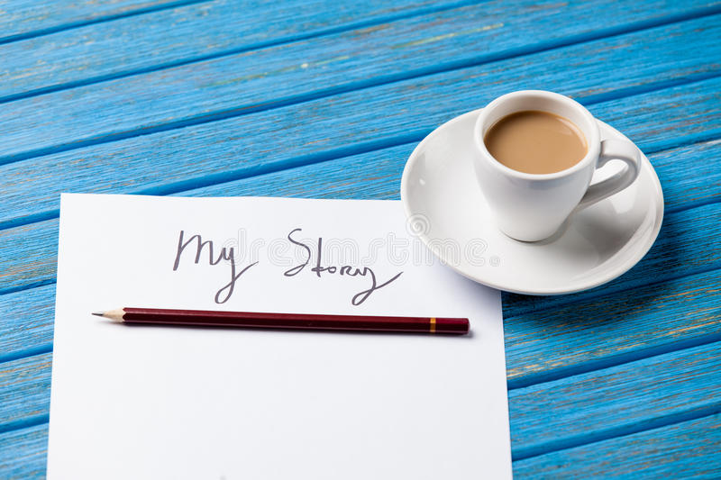 Pencil and paper with My Story words near cup of coffee. On blue wooden table royalty free stock images