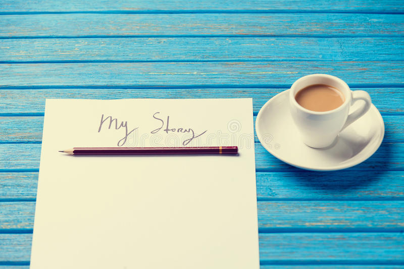 Pencil and paper with My Story words near cup of coffee. On blue wooden table royalty free stock photo