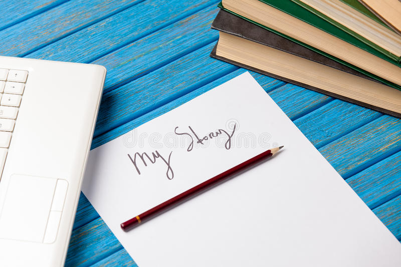 Pencil and paper with My Story words near notebook. On blue wooden table stock photo