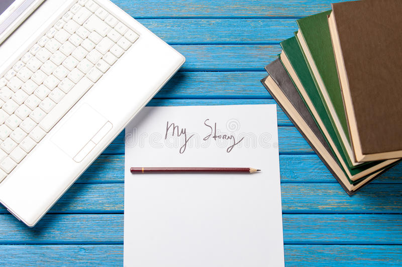 Pencil and paper with My Story words near notebook. On blue wooden table stock images
