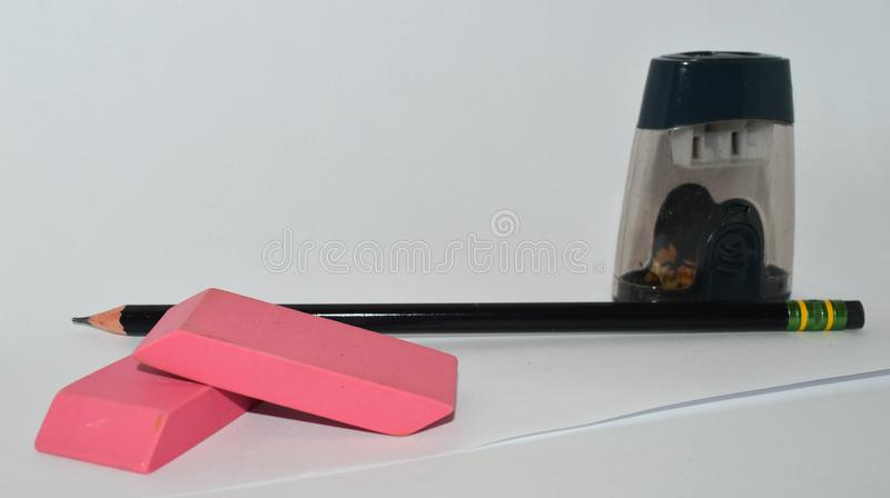 A pencil, pencil sharpener and two pink erasers royalty free stock image