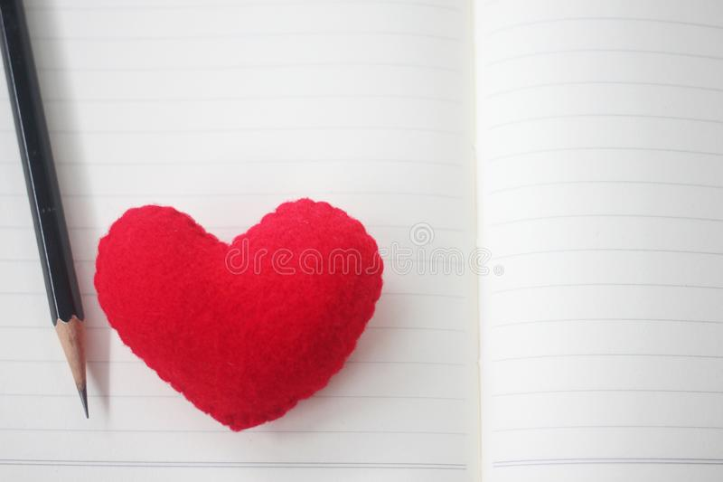 A pencil and a red heart are placed on an empty book. For design in Love and valentine day royalty free stock photo