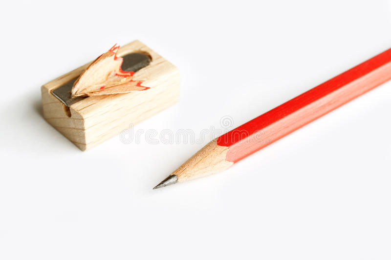 Pencil sharpener. Close up of a red pencil with sharpener over white background royalty free stock images
