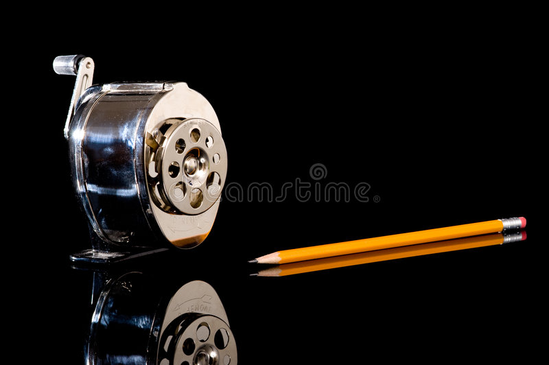 Pencil Sharpener and Pencil. A pencil sharpener and a yellow pencil on a black background with copy space stock images