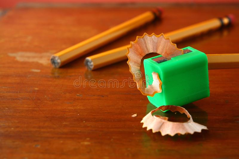 Pencil in a sharpener and two unsharpened pencils royalty free stock photos