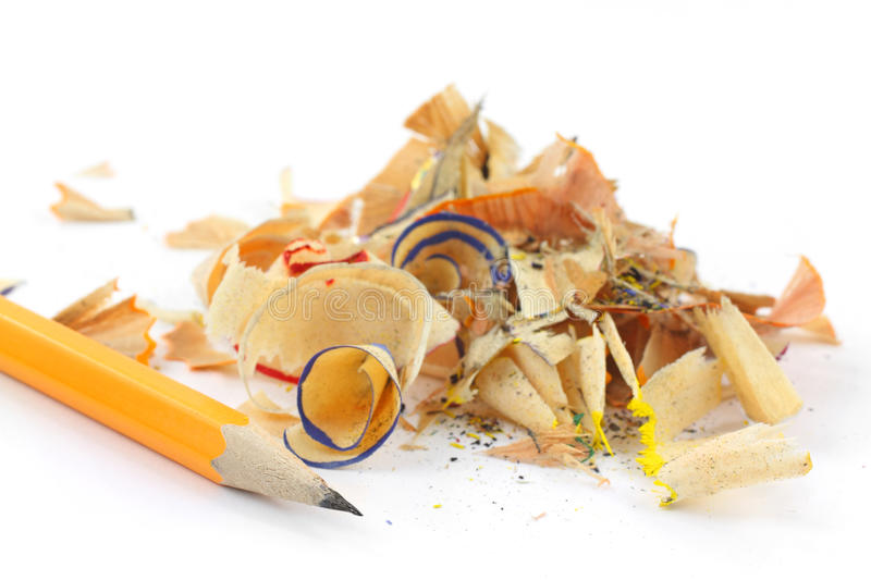 Pencil shavings with pencil. A small mound of pencil shavings with a sharpened lead pencil on a white background royalty free stock photos