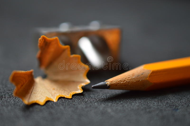Pencil with shavings and sharpener up close stock photography