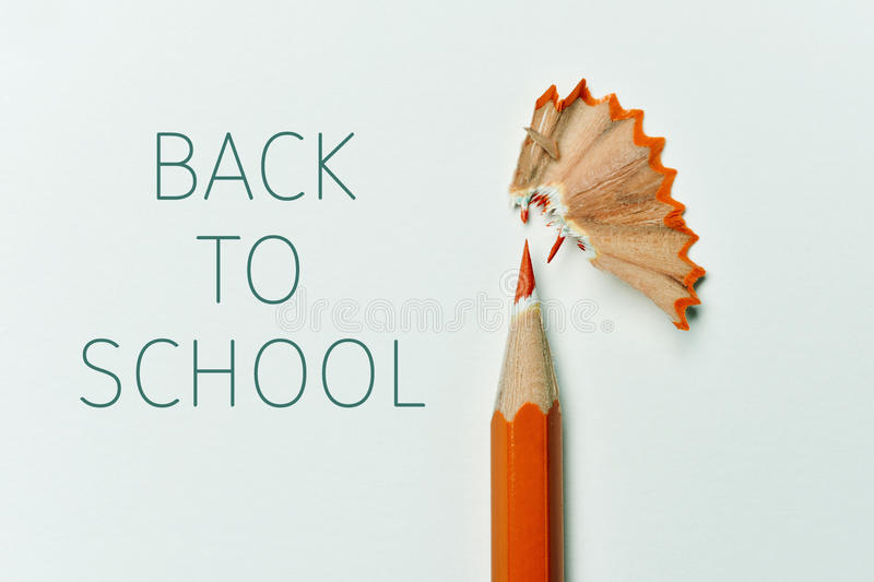 Pencil, shavings and text back to school. Closeup of an orange pencil crayon freshly sharpened, fan-shaped shavings and the text back to school on an off-white royalty free stock photography