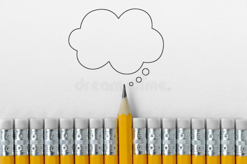 Pencil tip standing out from croud of pencil rubber erasers with empty thought bubble. On white paper stock image