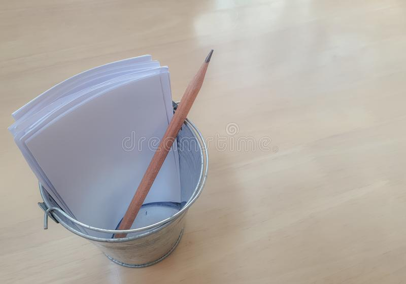 Pencil and white papers in the tiny steel pencil holder royalty free stock image