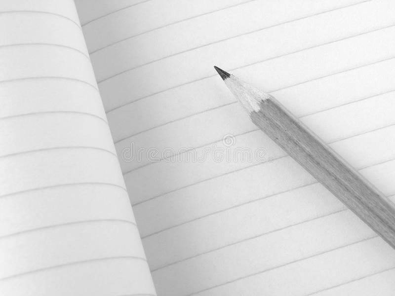 Pencil and workbook. Pencil and open workbook fragment in black and white stock images