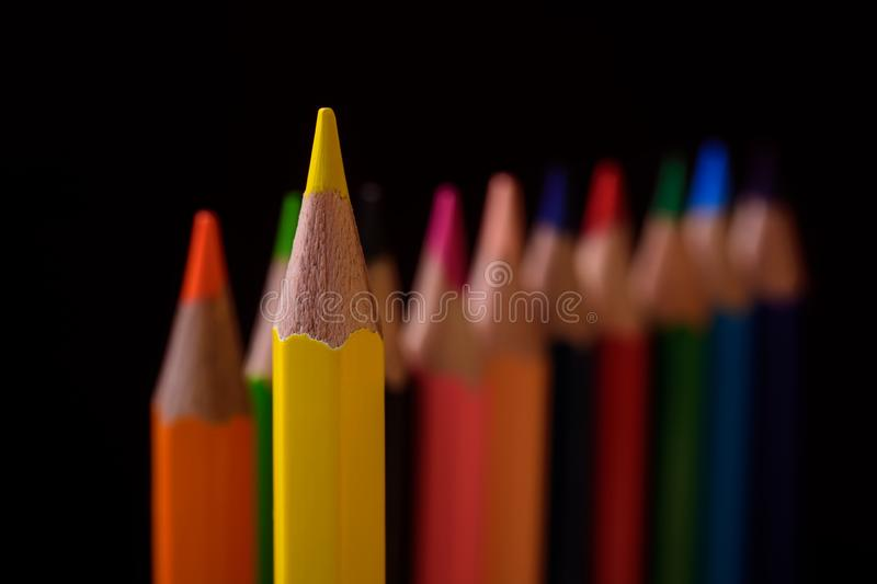 Yellow pencil is the leader. Among other pencils. Red background. Concept in business stock photo