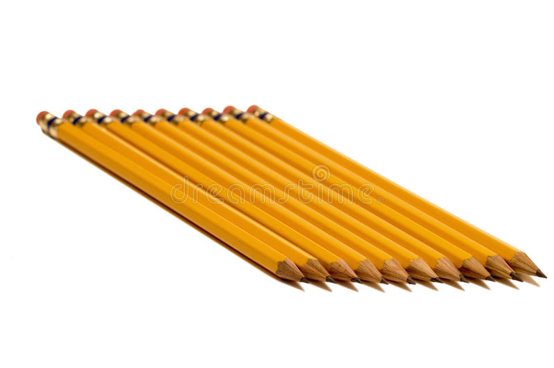 Pencils On An Angle. Horizontal shot of a row of yellow pencils sharpened with shadows. Isolated on white. Focus on the foreground stock images