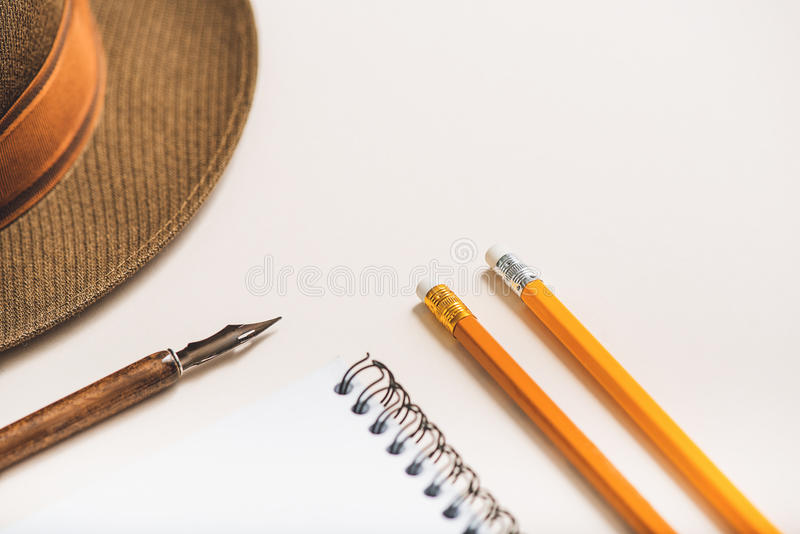 Pencils beside brown elegant hat. Open notebook between implements for writing. Fedora headwear is near fountain pen stock photography