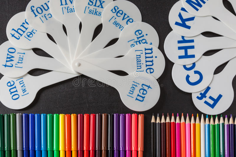 Pencils and cards of numerals from one to ten with transcription and consonant letters of alphabet on the black school chalkboard. Back to school background with royalty free stock image