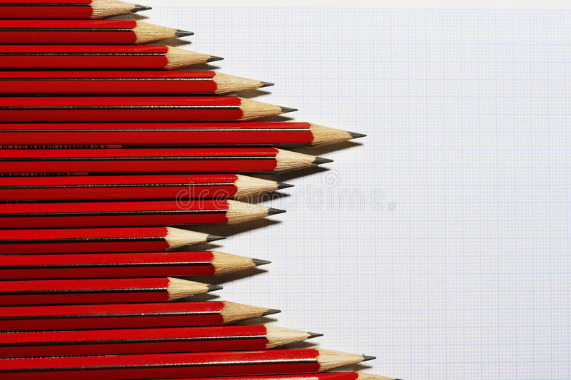 Pencils forming bar graph pattern on graph paper view from above stock photo