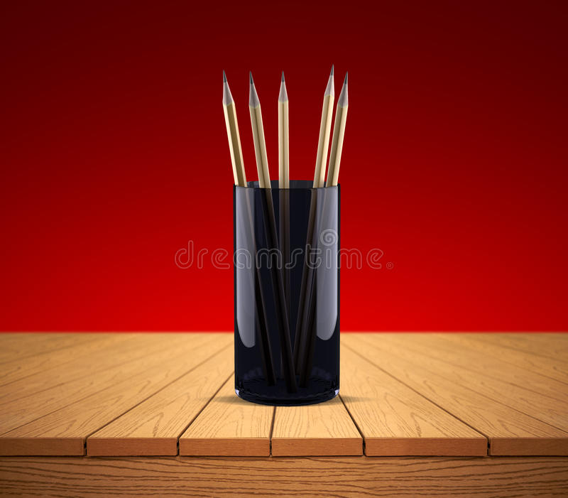 Pencils in a glass on a wooden table stock photo
