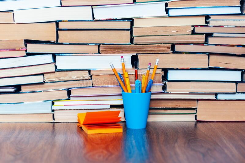 Pencils in holder, note paper and stack of books, school background for education learning concept.  royalty free stock photography