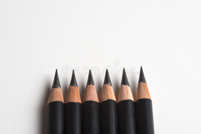 Sharpened black pencils in a horizontal row stock images