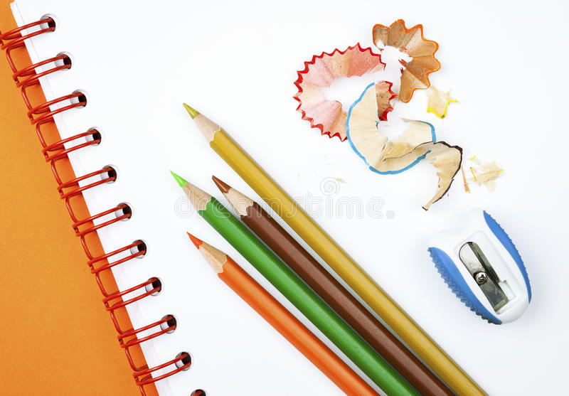 Pencils and sharpener. Four colorful pencils with sharpener and shavings on white notebook stock photo