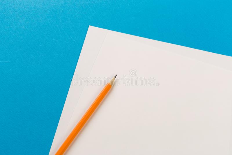 Pencils with white paper sheets on coloured background royalty free stock photo