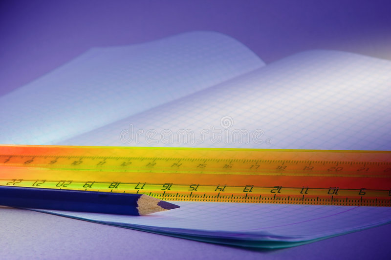 Pencils and writing-book. Ruler and dark blue pencil on a background of an open writing-book royalty free stock photos