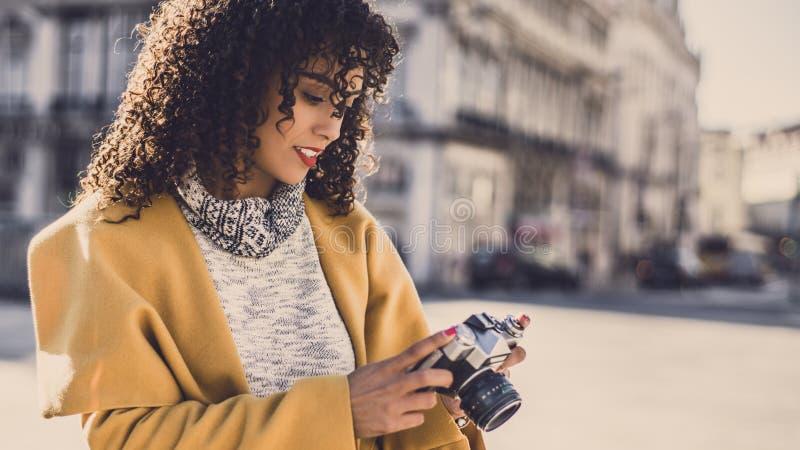 Pencive krullend brunette met retro camera royalty-vrije stock afbeelding