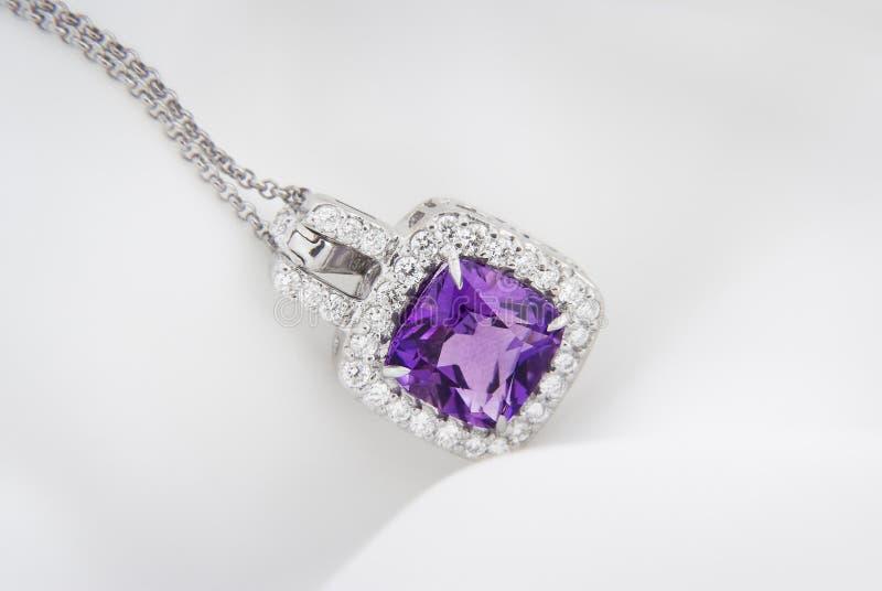 Pendant d'or blanc avec l'améthyste violette de rose et diamants sur le sof photo stock