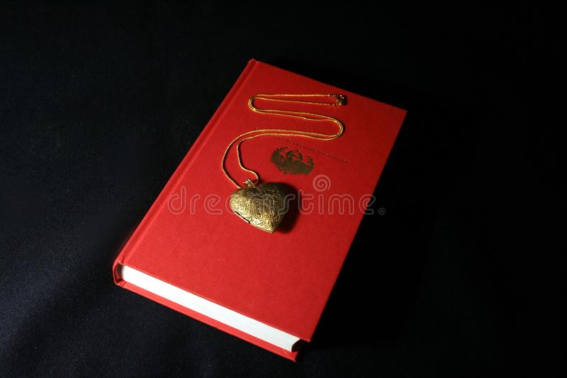 Pendant d'or sous forme de coeur sur un fond rouge, photo stock