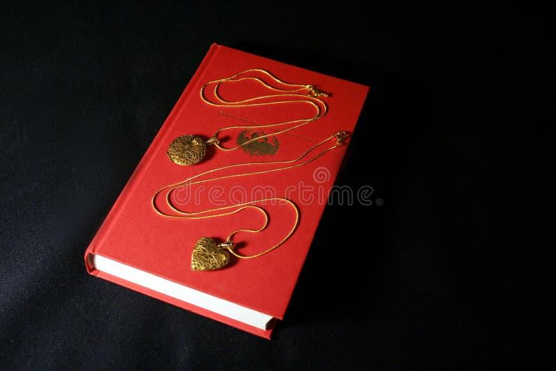 Pendant de l'or deux sur le fond du livre rouge photographie stock