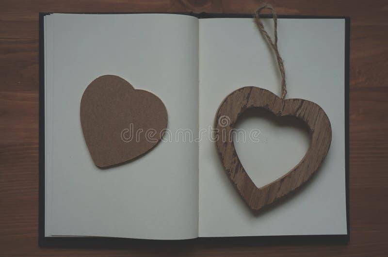 Pendant en bois de forme de coeur de Brown sur le livre blanc photos libres de droits