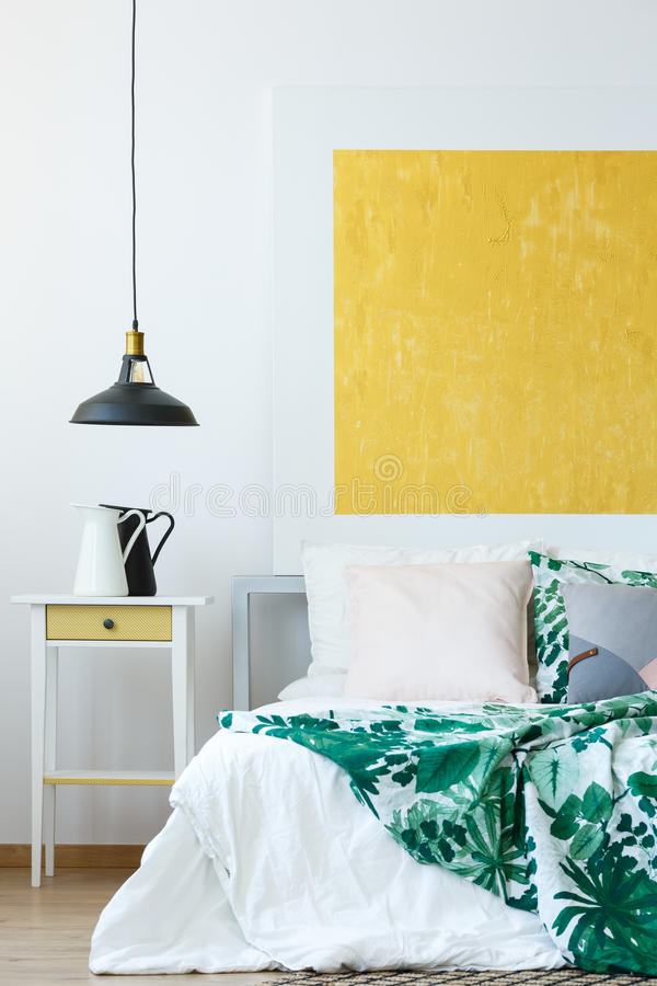 Pendant lamp and wall decor. Pendant lamp, tropical bedclothes and yellow abstract wall decor royalty free stock images