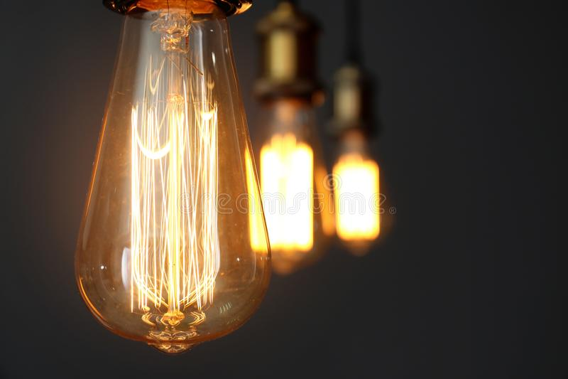 Pendant lamps with light bulbs on grey background, closeup. Space for text royalty free stock photos