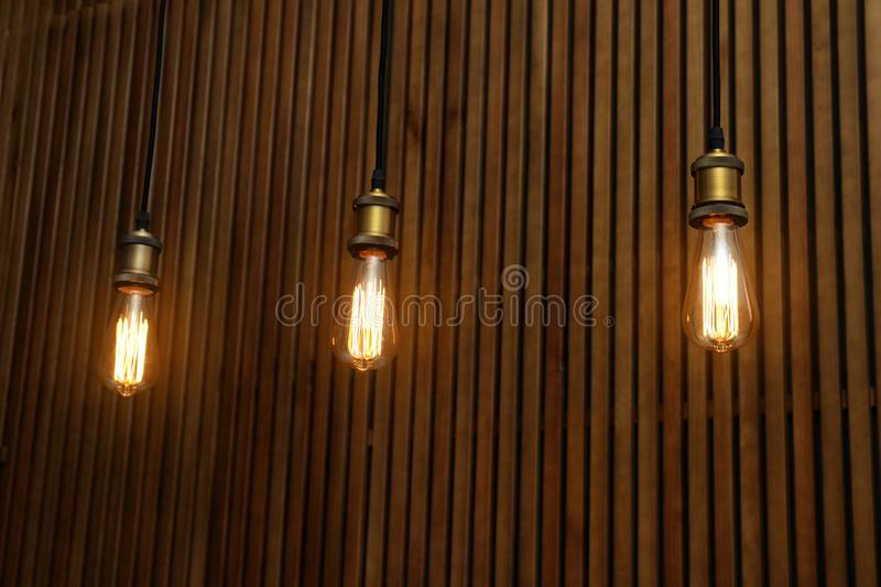 Pendant lamps with light bulbs. On wooden background stock images