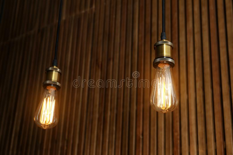 Pendant lamps with light bulbs. On wooden background royalty free stock images